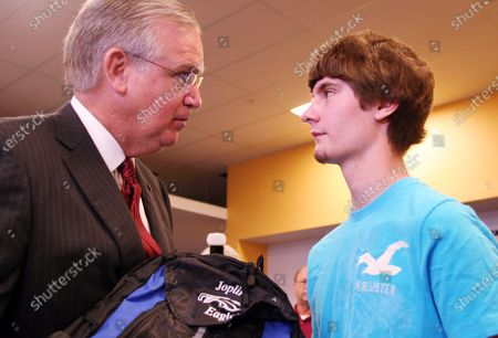 Stock Photo of Mo. Gov. Jay Nixon hands the first computer to senior Quinton Anderson on opening day of school in Joplin, Missouri on August 17, 2011. Anderson, who was critically injured in the May 22 tornado that killed 160 people, lost both parents in the storm. Free laptops were distributed to students at Joplin High School as part of a $1 million gift from the United Arab Emirates.