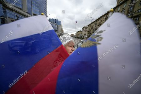 An elderly woman, one of people who turned up to oppose a hard-line Soviet coup in August 1991, holds Russian national flags marking the 30th anniversary of the failed coup and Russia Day of The National Flag in Moscow, Russia, . The world held its breath 30 years ago when a group of top Communist officials ousted Soviet leader Mikhail Gorbachev and flooded Moscow with tanks. But instead of bringing a rollback of liberal reforms and a return to Cold War confrontations, the August 1991 coup collapsed in just three days and precipitated the breakup of the Soviet Union a few months later