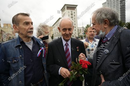 Russian human rights activist Lev Ponomarev, left, Sergei Nefyodov, center, and other elderly people who turned up to oppose a hard-line Soviet coup in August 1991, talk to each other as they gather to mark the 30th anniversary of the failed coup and Russia Day of The National Flag in Moscow, Russia, . The world held its breath 30 years ago when a group of top Communist officials ousted Soviet leader Mikhail Gorbachev and flooded Moscow with tanks. But instead of bringing a rollback of liberal reforms and a return to Cold War confrontations, the August 1991 coup collapsed in just three days and precipitated the breakup of the Soviet Union a few months later