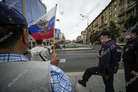 Man, one of people who turned up to oppose a hard-line Soviet coup in August 1991, holds a Russian national flag marking the Russia Day of The National Flag, as two police officers stand next at a memorial to three men killed in the August 1991 hard line Communist coup attempt in Moscow, Russia, . The world held its breath 30 years ago when a group of top Communist officials ousted Soviet leader Mikhail Gorbachev and flooded Moscow with tanks. But instead of bringing a rollback of liberal reforms and a return to Cold War confrontations, the August 1991 coup collapsed in just three days and precipitated the breakup of the Soviet Union a few months later