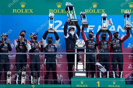 Toyota Gazoo Racing drivers Mike Conway of Britain, Kamui Kobayashi of Japan and Jose Maria Lopez of Argentina, at right, lift their trophies after winning the 24-hour Le Mans endurance race, in Le Mans, France, . At left is the second placed team of Toyota Gazoo Racing's drivers Sebastien Buemi of Switzerland, Kazuki Nakajima of Japan and Brendon Hartley of New Zeland