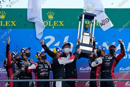 Toyota Gazoo Racing drivers Mike Conway of Britain, Kamui Kobayashi of Japan and Jose Maria Lopez of Argentina, at right, lift the trophy after winning the 24-hour Le Mans endurance race, in Le Mans, France, . At left is the second placed team of Toyota Gazoo Racing drivers Sebastien Buemi of Switzerland, Kazuki Nakajima of Japan and Brendon Hartley of New Zeland