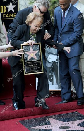 The late Buddy Holly receives a posthumous Walk of Fame Star on his 75th birthday on Vine Street in front of The Capitol Records Building in Los Angeles on September 7, 2011. His widow, Maria Elena Holly trips on the carpet as Gary Busey catches her during the star dedication ceremony.