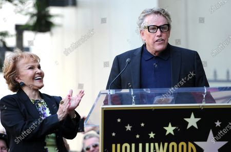"""The late Buddy Holly received a posthumous Walk of Fame Star on his 75th birthday on Vine Street in front of The Capitol Records Building in Los Angeles on September 7, 2011. His widow, Maria Elena Holly who made a rare appearance at the event, listens as Gary Busey puts on """"Buddy Holly"""" style glasses and says a few words. Busey starred as Holly in the move The Buddy Holly Story."""