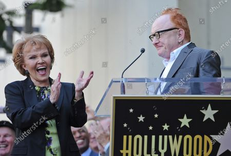 """The late Buddy Holly received a posthumous star on Hollywood's Walk of Fame on his 75th birthday on Vine Street in front of The Capitol Records Building in Los Angeles on September 7, 2011. His widow, Maria Elena Holly who made a rare appearance at the event, listens as record producer Peter Asher puts on """"Buddy Holly"""" style glasses and says a few words."""