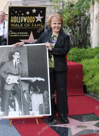 Maria Elena Holly stands near a photo of her late husband next to his star of the Walk of Fame as the late Buddy Holly received a posthumous Walk of Fame Star on his 75th birthday on Vine Street in front of The Capitol Records Building  in Los Angeles on September 7, 2011.