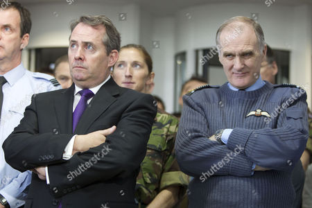 Stock Image of Liam Fox and Sir Jock Stirrup listen to Prime Minister David Cameron's address to staff at PJHQ