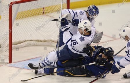 St. Louis Blues Scott Nichol and Toronto Maple Leafs Clarke MacArthur slide into Leafs goaltender Ben Scrivens as the two chase the puck in the first period at the Scottrade Center in St. Louis on November 10, 2011.