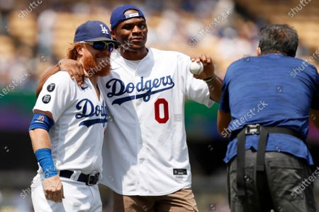 New Los Angeles Lakers NBA player Russell Westbrook, center, poses for photo with Los Angeles Dodgers' Justin Turner, left, after throwing out the first ceremonial pitch, before a baseball game against the New York Mets in Los Angeles