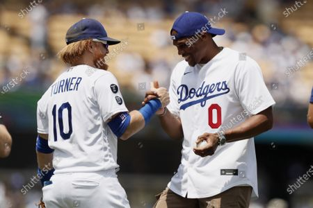 New Los Angeles Lakers NBA player Russell Westbrook, right, celebrates with Los Angeles Dodgers' Justin Turner after throwing out the first ceremonial pitch before a baseball game against the New York Mets in Los Angeles