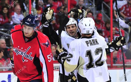 Pittsburgh Penguins' Craid Adams (C) celebrates with teammate Richard Park (12) next to Washington Capitals' Jeff Schultz after Adams scored in the first period at the Verizon Center in Washington on December 1, 2011.