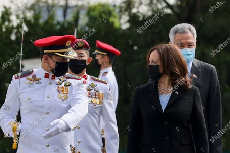 Vice President Kamala Harris, front right, prepares to inspect an honor guard with Singapore's Prime Minister Lee Hsien Loong, rear right, at the Istana in Singapore