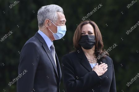 Vice President Kamala Harris, right, stands next to Singapore's Prime Minister Lee Hsien Loong during a welcome ceremony at the Istana in Singapore
