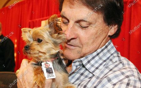 Former St. Louis Cardinals manager Tony La Russa cuddles with Ellie, a two year old miniture yorkie during the team's Winter Warm Up in St. Louis on January 15, 2012. Ellie was brought to the event by her owner Sandi Jackson of Fenton, Missouri.