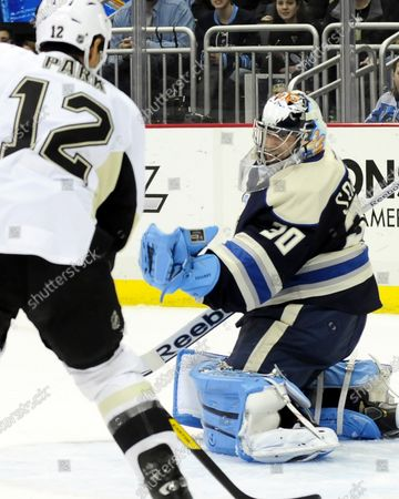 Columbus Blue Jacket goalie Curtis Sanford makes a glove save as Pittsburgh Penguins Richard Park looks on in the second shot  at the Consol Energy Center in Pittsburgh on February 26, 2012.