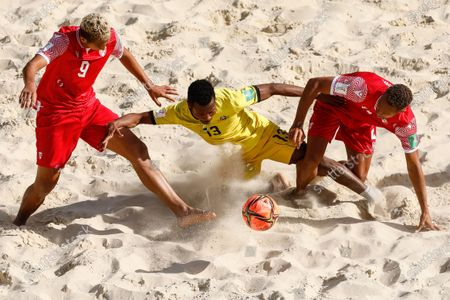 Dez (C) of Mozambique vies for the ball with Heirauarii Salem (L) and Dylan Paama of Tahiti during the FIFA Beach Soccer World Cup Russia 2021 Group D match between Tahiti and Mozambique on August 23, 2021 at Luzhniki Beach Soccer Stadium in Moscow, Russia.