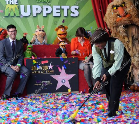Walt Disney Studios President Rich Ross,looks on as a woman sweeps confetti off the Inimitable Muppets star during an unveiling cefremony honoring The Muppets with the 2,466th star on the Hollywood Walk of Fame in Los Angeles on March 20, 2012.