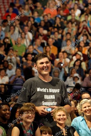 Igor Vovkovinskiy, 27, of Rochester, Minn, standing 7-feet and 8-inches tall, listens to President Barack Obama, not pictured, during a health insurance reform rally in Minneapolis. Vovkovinskiy, the tallest man in the United States, has died in Minnesota. He was 38. His family says the Ukrainian-born Vovkovinskiy died of heart disease, at the Mayo Clinic in Rochester