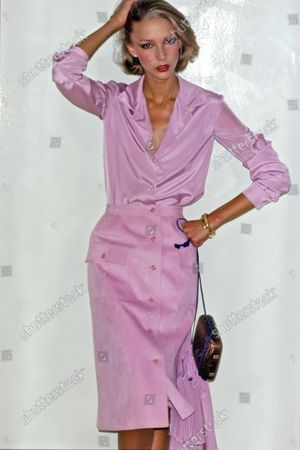 Model Karen Bjornson wearing Halston's Spring 1976 collection, right hand on her head and left fist on her hip, posed in front of a white wall. She is wearing a purple ultrasuede button front knee length skirt from Springs Mills fabric with a purple silk crepe de Chine blouse. Accessories: earrings, bracelets, purse by Halston.