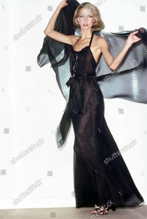Model Karen Bjornson wearing Halston's Spring 1976 collection, both hands raised to extend a shawl out behind her, posed in front of a white wall. She is wearing an evening jumpsuit of black chiffon Pomezia fabric with a halter-top slit almost to the waist, with a tiny ruffle along the edge, wide legs, and a black chiffon shawl. Accessories: shoes by Halston. Karen Bjornson