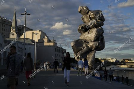 """People walk next to """"Big Clay #4"""" artwork by the Swiss artist Urs Fischer on Bolotnaya embankment in Moscow, Russia, . A 12-meter aluminum sculpture copies forms of an ordinary hunk of clay and reveals the artist's magnified palm creases and fingerprints"""