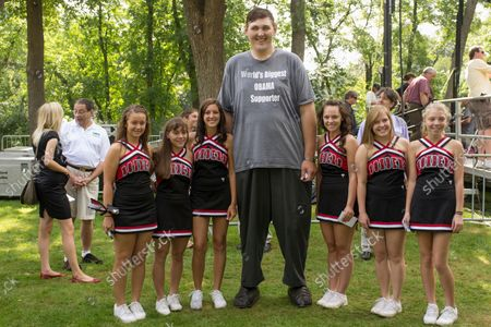 In this Aug. 15, 2011 photo, Seven-foot, eight-inch tall, Igor Vovkovinskiy, the self proclaimed biggest supporter of President Barack Obama, takes a photo with cheerleaders from the Cannon Falls high school prior to a President Barack Obama town hall event at Lower Hannah's Bend Park, in Cannon Falls, Minn. Vovkovinskiy, the tallest man in the United States, has died in Minnesota. He was 38. His family says the Ukrainian-born Vovkovinskiy died of heart disease, at the Mayo Clinic in Rochester