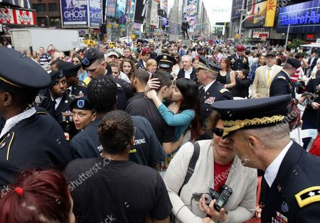 A United States Army recruit embraces and kisses a girl after being sworn in by U.S. Chief of Staff Gen. Raymond T. Odierno accompanied by the U.S. Army Band in Times Square on Flag Day in New York City on June 14 2012.