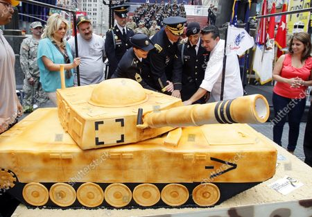 U.S. Army Chief of Staff Gen. Raymond T. Odierno cuts a tank shaped cake before he swears in United States Army recruits, accompanied by the U.S. Army Band in Times Square on Flag Day in New York City on June 14 2012.