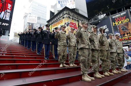 Eixisting members of the U.S. Army raise their hands and watch as Chief of Staff Gen. Raymond T. Odierno (R) swears in United States Army recruits, accompanied by the U.S. Army Band in Times Square on Flag Day in New York City on June 14 2012.