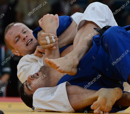 Dimitri Peters of Germany (White) puts a leg lock on gold medalist Tagir Khaibulaev of Russia in Men's 100KG Judo in the semifinals at the ExCel center at the London 2012 Summer Olympics on August 2, 2012 in London.  The Russians took gold in Men's 100kg.