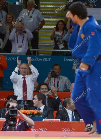 Russian President Vladimir Putin applauds gold medalist Tagir Khaibulaev of Russia at the Judo venue at the ExCel center at the London 2012 Summer Olympics on August 2, 2012 in London.  The Russians took gold in Men's 100kg.