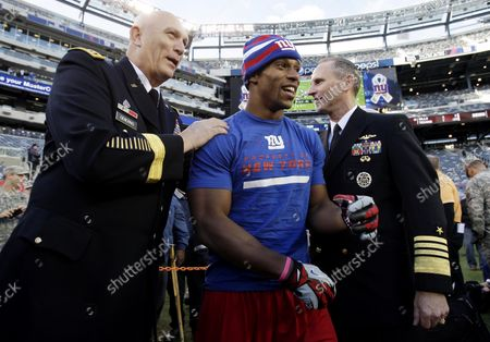 """Chief of Naval Operations Admiral Jonathan W. Greenert and the 38th Chief of Staff of the U.S. Army Raymond T. """"Ray"""" Odierno stand with New York Giants Victor Cruz on the field before the New York Giants play the Pittsburgh Steelers in week 9 of the NFL season at MetLife Stadium in East Rutherford, New Jersey on November 4, 2012. The game comes just 5 days after Hurricane Sandy strikes the north east section of the United States."""