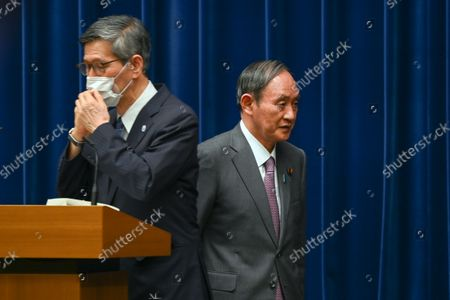 Japan's Prime Minister Yoshihide Suga (R) leaves after a news conference with chairman of the government's pandemic advisory panel Shigeru Omi (L) at the prime minister's official residence in Tokyo, Japan, 25 August 2021.