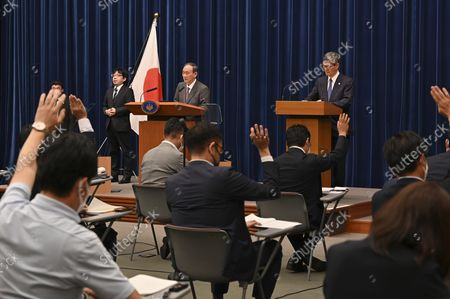 Japan's Prime Minister Yoshihide Suga (top, L) attends a news conference with chairman of the government's pandemic advisory panel Shigeru Omi (top, R) at the prime minister's official residence in Tokyo, Japan, 25 August 2021.