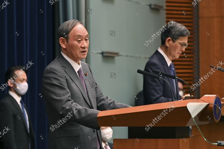 Japan's Prime Minister Yoshihide Suga (L) attends a news conference with chairman of the government's pandemic advisory panel Shigeru Omi (R) at the prime minister's official residence in Tokyo, Japan, 25 August 2021.