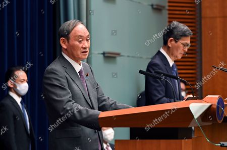 Japan's Prime Minister Yoshihide Suga, left, attends a news conference with chairman of the government's pandemic advisory panel Shigeru Omi at the prime minister's official residence in Tokyo, . Japan has expanded its coronavirus state of emergency for a second week in a row, adding eight more prefectures as a surge in infections fueled by the delta variant strains the country's health care system