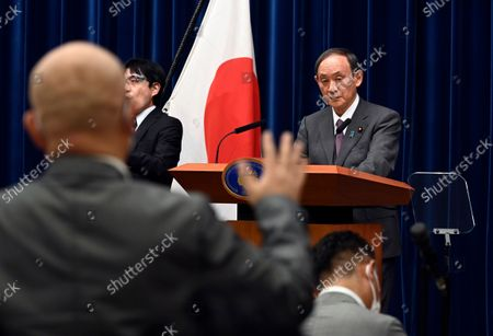 Japan's Prime Minister Yoshihide Suga attends a news conference with chairman of the government's pandemic advisory panel Shigeru Omi, not pictured, at the prime minister's official residence in Tokyo, . Japan has expanded its coronavirus state of emergency for a second week in a row, adding eight more prefectures as a surge in infections fueled by the delta variant strains the country's health care system