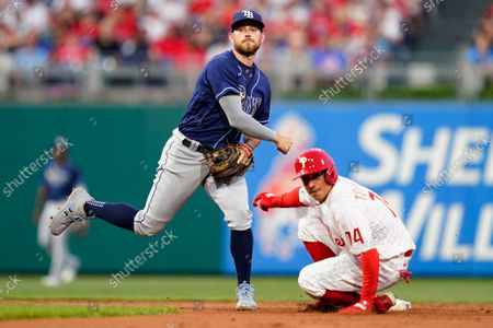 Stock Image of Tampa Bay Rays second baseman Brandon Lowe, left, throws to first base after forcing out Philadelphia Phillies' Ronald Torreyes at second on a run-scoring double play hit into by Luke Williams during the second inning of an interleague baseball game, in Philadelphia