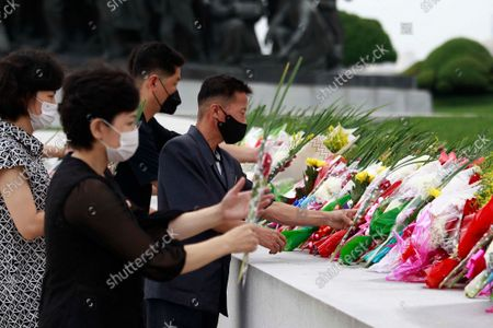 Stock Picture of Citizens lay bouquets of flowers at statues of the late leaders Kim Il Sung and Kim Jong Il on Mansu Hill on the occasion of the 61st anniversary of Kim Jong Il's first field guidance for the revolutionary armed forces in Pyongyang, North Korea