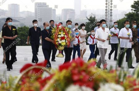 Stock Image of Citizens visit statues of the late leaders Kim Il Sung and Kim Jong Il on Mansu Hill on the occasion of the 61st anniversary of Kim Jong Il's first field guidance for the revolutionary armed forces in Pyongyang, North Korea