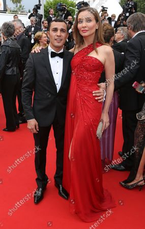 """Brahim Asloum (L) and Isabella Orsini arrive on the red carpet before the screening of the film """"Inside Llewyn Davis"""" during the 66th annual Cannes International Film Festival in Cannes, France on May 19, 2013."""