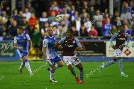 Carney Chukwuemeka of Aston Villa in action with Barrow's Jason Taylor  during the Carabao Cup 2nd round match between Barrow and Aston Villa at Holker Street, Barrow-in-Furness on Tuesday 24th August 2021.
