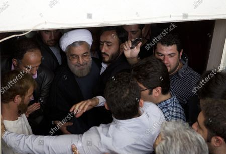Stock Picture of Moderate presidential candidate and former top nuclear negotiator Hassan Rohani is surrounded by supporters during his presidential campaign rally in Tehran, Iran on May 30, 2013.  The United States has questioned the credibility of Iran's June 14th election due to the disqualification of former president Akbar Hashemi Rafsanjani and reform candidates Mir Hossein Mousavi and Mehdi Karroubi, who remain under house arrest following the elections in 2009.