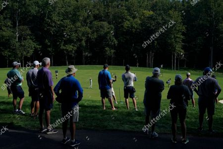 Kevin Streelman, center left, hits from the second fairway as spectators look on during the first round of the BMW Championship golf tournament, at Caves Valley Golf Club in Owings Mills, Md
