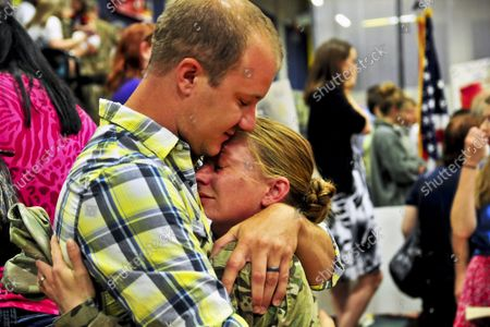 Army Spc. Jessie Nelson hugs her husband, Matt, on Joint Base Lewis-McChord, in Washington, July 10, 2013. Nelson and about 230 soldiers returned home after an eight-month deployment to Afghanistan to support Operation Enduring Freedom. Nelson is an all-source intelligence analyst assigned to the 2nd Infantry Division's Headquarters Company, 4th Stryker Brigade Combat Team.
