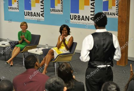 First Lady Michelle Obama (C) and Chicago First Lady Amy Rule (L) applaud as Urban Alliance student Steven O'Neal Jr. tells about his experiences at Columbia College in Chicago on July 18, 2013. With her visit, the First Lady seeks to bring attention to programs like Urban Alliance which is a year-long career education and employment program for underserved high school seniors that provides paid internships, formal training, and mentoring.