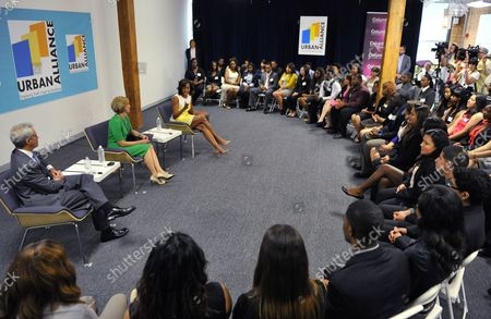 First Lady Michelle Obama (R) along with Chicago Mayor Rahm Emanuel (L) and Chicago First Lady Amy Rule talk with students involved with Urban Alliance at Columbia College in Chicago on July 18, 2013. With her visit, the First Lady seeks to bring attention to programs like Urban Alliance which is a year-long career education and employment program for underserved high school seniors that provides paid internships, formal training, and mentoring.