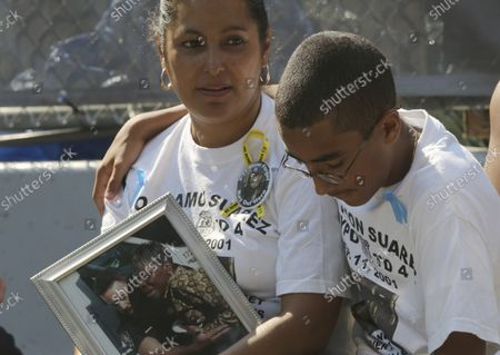 Stock Image of Annie, left, and Jason Ortiz, hold a photo of close family friend police officer Ramon Suarez rescuing Crystal Tyson while paying their respects to him near the south reflecting pool of the 9/11 Memorial during ceremony marking the 12th anniversary of the 9/11 attacks on the World Trade Center in New York, Wednesday, Sept. 11, 2013.