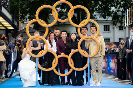 Actors from left to right Fala Chen, producer Jonathan Schwartz, Michelle Yeoh, Fiorian Munteanu, Simu Liu, Awkwafina, Benedict Wong, and Director Destin Daniel Cretton, peer through the rings as they pose for photographs on the red carpet for the premiere of Shang-Chi, at a cinema in west London