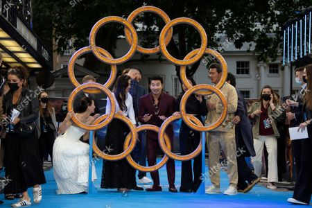 Stock Picture of Actors from left to right Fala Chen, producer Jonathan Schwartz, Michelle Yeoh, Fiorian Munteanu, Simu Liu, Awkwafina, Benedict Wong, and Director Destin Daniel Cretton, peer through the rings as they pose for photographs on the red carpet for the premiere of Shang-Chi and the Legend of the Ten Rings, the first Marvel film to feature an Asian superhero as the lead character, at a cinema in west London